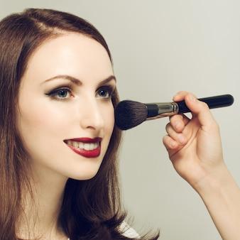 Молодая женщина в салоне красоты. нанесение макияжа. отфильтрованное изображение