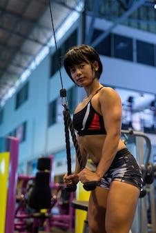 ロープで上腕三頭筋のプッシュダウンを行うジムの若い女性