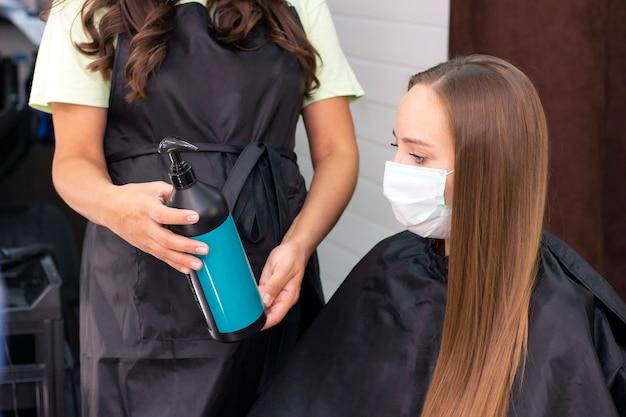 コロナウイルスのパンデミックのために保護マスクを身に着けている美容院で若い女性