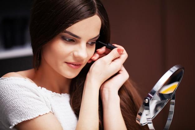Молодая женщина дома наносит макияж на лицо в спальне перед зеркалом.