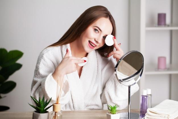 自宅の若い女性が鏡の前のバスルームの顔に化粧をします。
