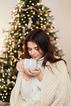 Молодая женщина дома во время рождества, пьет горячий напиток из кружки