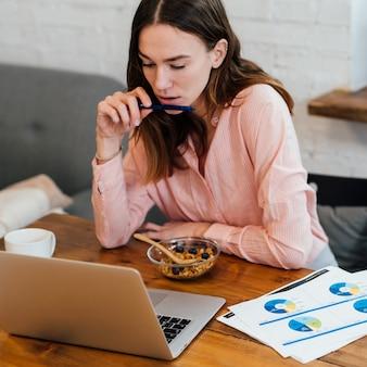 Молодая женщина дома за своим столом с ноутбуком.