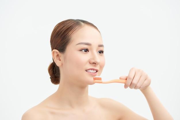 Молодая женщина дома чистит зубы утром