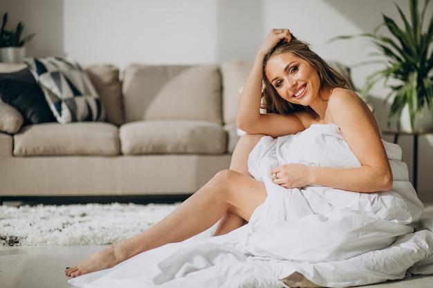 Молодая женщина дома покрыта одеялом