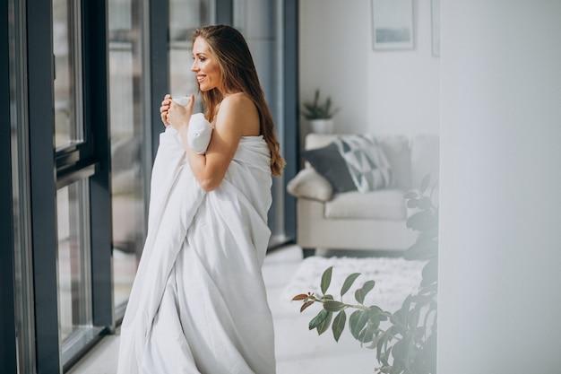 自宅で若い女性は毛布で覆われています。