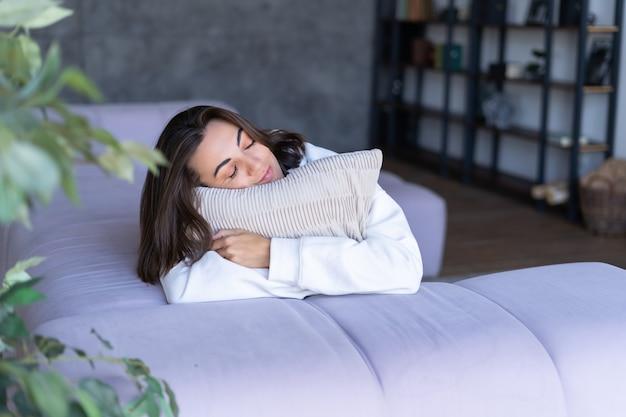 目を閉じて枕を静かに抱き締めるソファの上の白いパーカーで自宅で若い女性