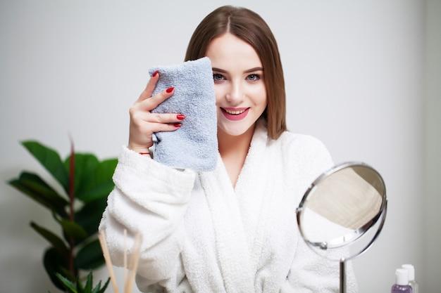 鏡の前で家にいる若い女性は、スパトリートメントの後に顔を拭きます。