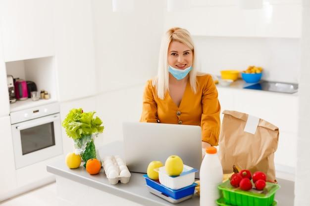 自己検疫注文製品のオンライン配信で自宅にいる若い女性。在宅勤務の検疫。コロナウイルス分離によるマスクされた家族の新生活。コンピューターでのリモート作業。パンデミックライフスタイル