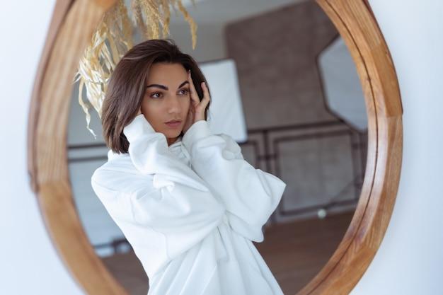 Молодая женщина дома в спальне в теплой белой толстовке с капюшоном позирует перед зеркалом