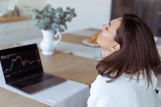 Молодая женщина дома на кухне в белом балахоне с ноутбуком, график на экране