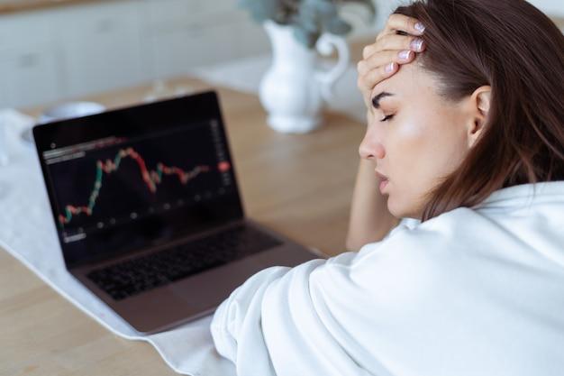 노트북이 있는 흰색 후드티를 입고 부엌에 있는 젊은 여성, 화면에 그래프
