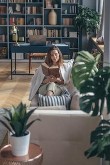 집에서 젊은 여자는 책과 함께 소파에 누워있다.