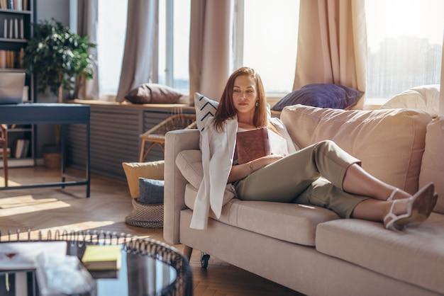 本を持ってソファに横になっている自宅の若い女性。