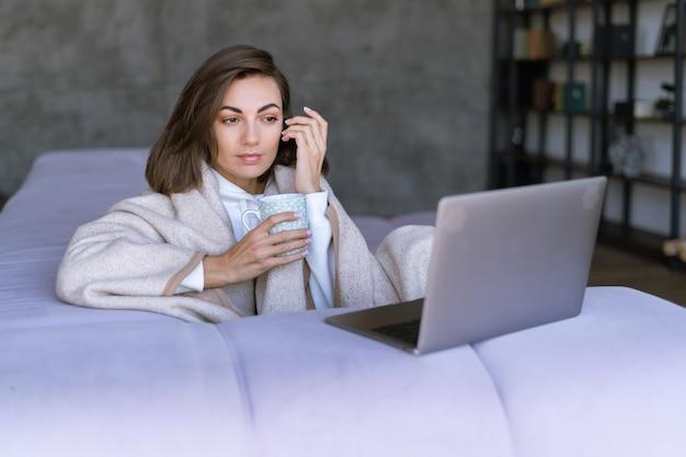 Молодая женщина дома на диване зимой под уютным пледом с ноутбуком, смотрит фильм