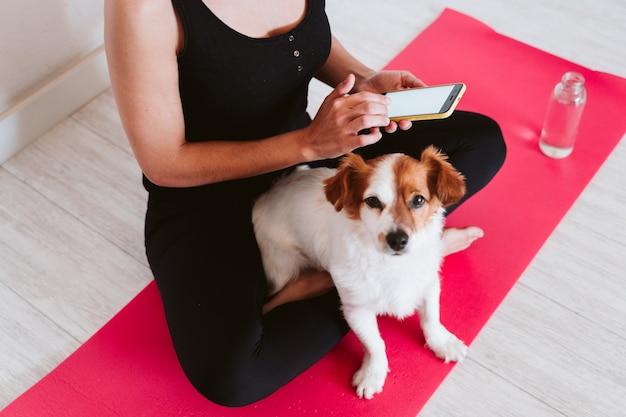 Молодая женщина у себя дома расслабилась с помощью передвижного дома. сидя на коврике для йоги со своей милой маленькой собачкой. технология и