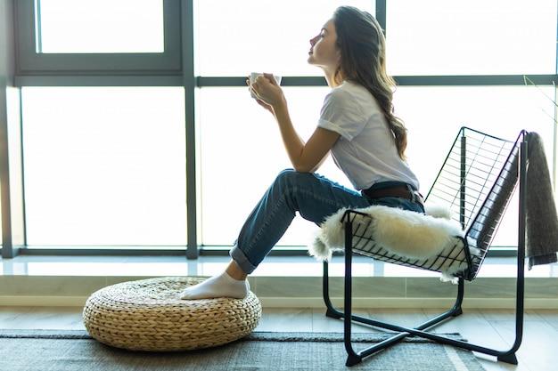 若い女性が自宅でコーヒーやお茶を飲んで彼女のリビングルームでリラックスできる窓の前にモダンな椅子に座って