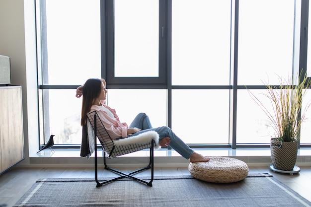 若い女性自宅で彼女のリビングルームでリラックスした窓の前でモダンな椅子に座って