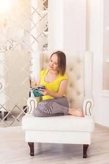 집에 있는 젊은 여성이 현대적인 의자에 앉아 책을 읽고 있습니다.