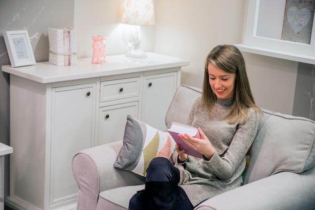 젊은 여자 집에서 그녀의 거실 읽기 책을 편안 하 게 현대의 자에 앉아. 홈 인테리어에 책을 읽는 젊은 여자