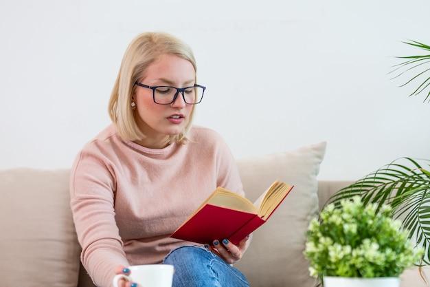 自宅で若い女性は、本を読んで彼女のリビングルームでリラックスしてコーヒーやお茶を飲んだり、モダンなソファに座っています。白い居心地の良いベッドと美しい少女、本を読んで、家の概念と快適さ