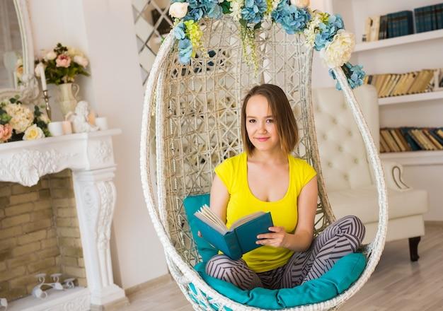집에 있는 젊은 여성이 흰색 의자에 앉아 거실에서 휴식을 취하고 책을 읽고 있습니다.