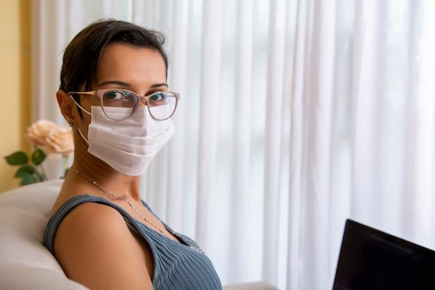 Молодая женщина дома носить защитную маску для профилактики вируса короны
