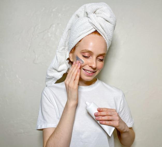 彼女の頭にタオルで自宅で若い女性
