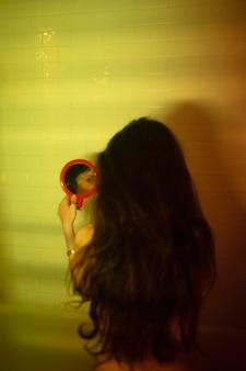 Молодая женщина дома с таинственными огнями в ванной