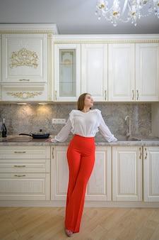 Молодая женщина в роскошном классическом белом интерьере кухни в стиле прованс