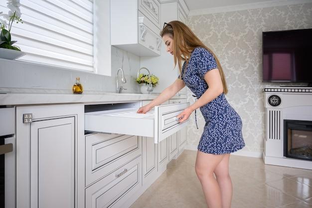Молодая женщина в роскошном современном классическом белом интерьере кухни