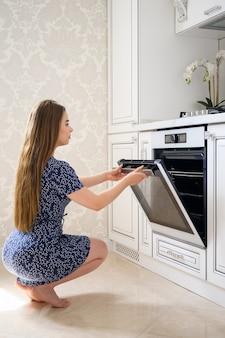 豪華でモダンな古典的な白いキッチンのインテリアで若い女性