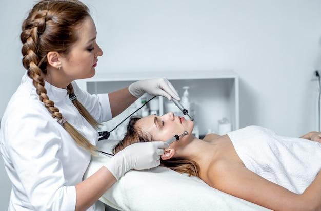 얼굴 자극 치료를 받고 스파 클리닉에서 젊은 여자. 미세 전류 치료 중 젊은 여성 얼굴 닫습니다.