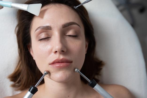 얼굴 자극 치료를 받고 스파 클리닉에서 젊은 여자
