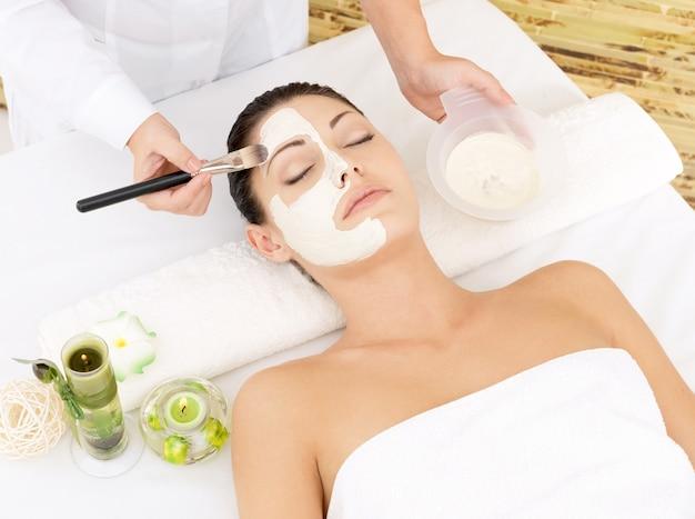 Молодая женщина в спа-салоне с косметической маской на лице. фото под большим углом
