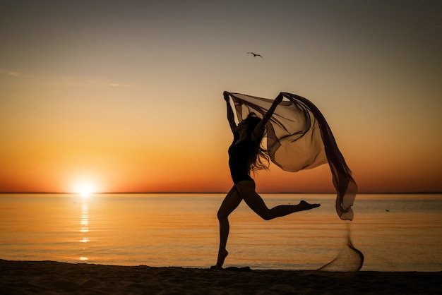 空の背景に布で海岸にジャンプする日没の若い女性