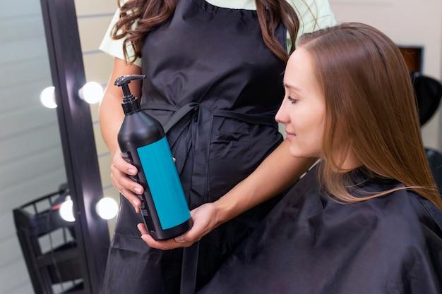 Молодая женщина в парикмахерской. парикмахер показывает шампунь для ухода за волосами