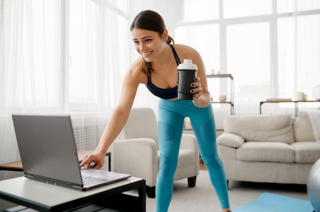 Молодая женщина за ноутбуком дома, онлайн-обучение фитнесу. женский человек в спортивной одежде, спортивная тренировка в интернете, интерьер комнаты