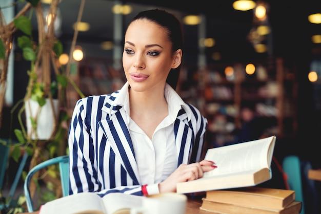 Молодая женщина в библиотеке. выпить кофе и почитать книгу. отдых и обучение, наслаждение книгой и кофе.