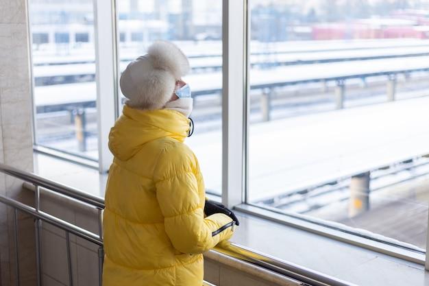 Молодая женщина на вокзале в защитной маске на лице в зимней одежде пассажира