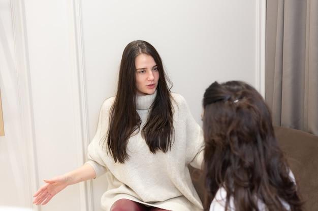 美容師のレセプションで若い女性、2人の女性がサロンのソファに座ってコミュニケーションを取り、手順を選択します