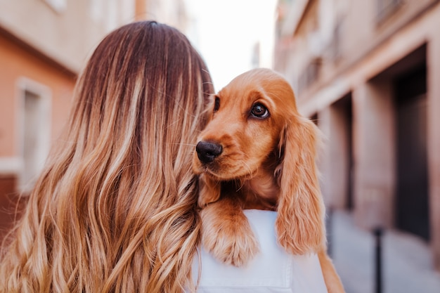 Молодая женщина на улице держит со своей милой собакой кокер-спаниель на плече образ жизни на природе с домашними животными