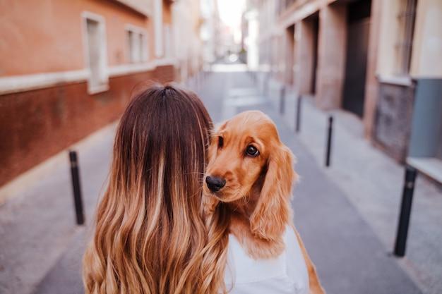 かわいいコッカー犬を肩に抱えて通りで若い女性。ペットと一緒にアウトドアライフスタイル