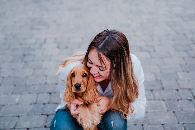 かわいいコッカー犬を抱き締める通りで若い女性。ペットと一緒にアウトドアライフスタイル