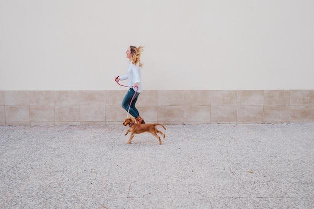 かわいいコッカー犬を連れて歩いて通りで若い女性。ペットと一緒にアウトドアライフスタイル