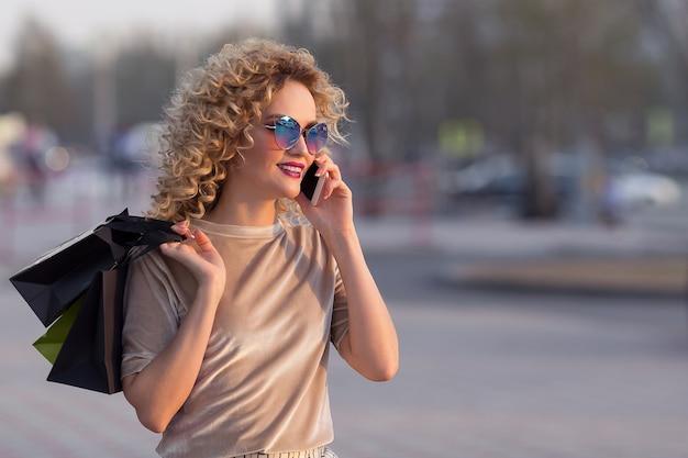 携帯電話で話している買い物袋を持つ通りの若い女性。