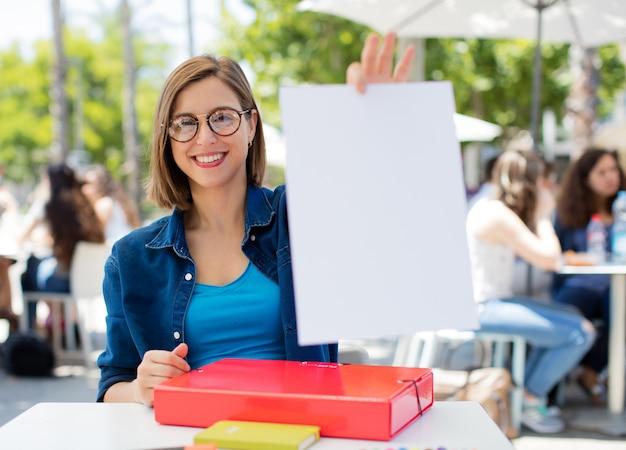 若い女性が大学にプラカードを持っています
