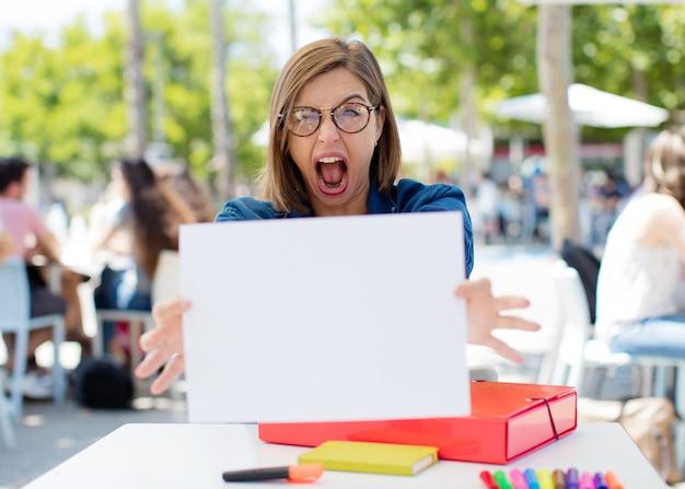 若い女性が大学にプラカードを持っています Premium写真