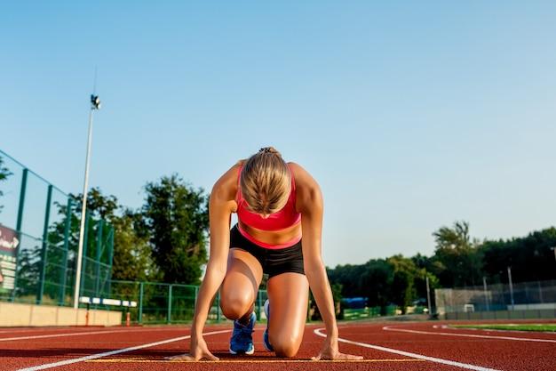 경마장에서 경주를 시작할 준비가 된 시작 위치에 있는 젊은 여성 운동선수