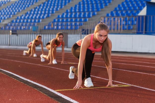 レースを開始する準備ができている開始位置で若い女性アスリート。